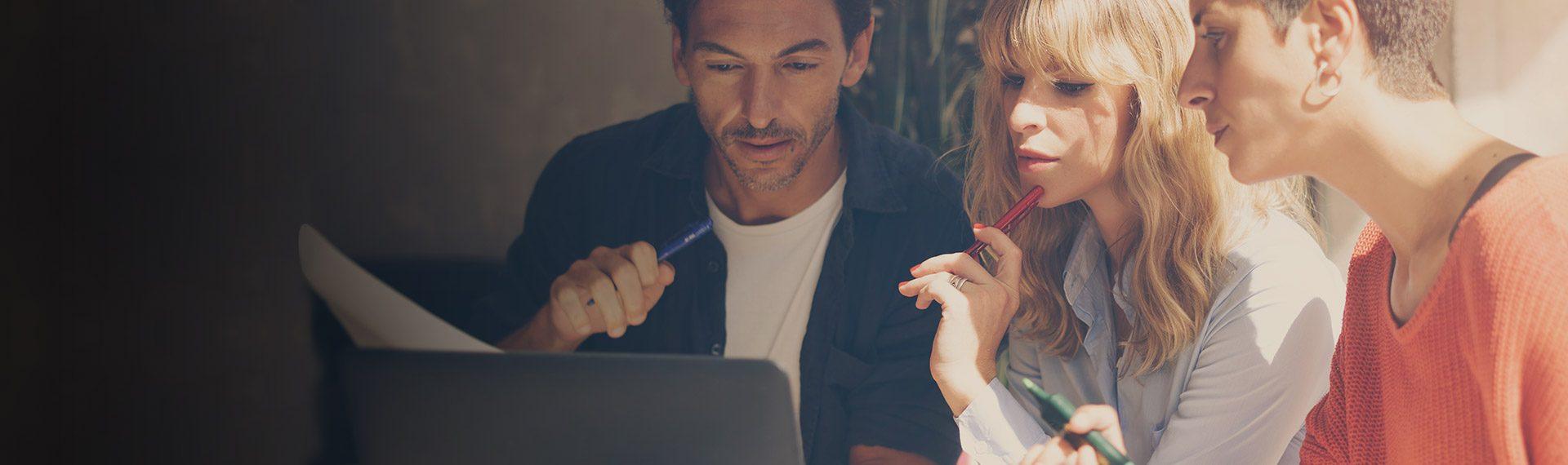 banner na stronie system ERP dla organizacji non profit - ludzie pracujący przy komputerze