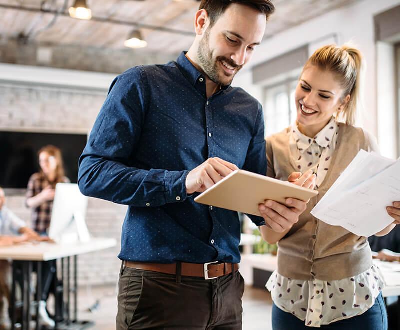 Mężczyzna i kobieta przeglądają dane na tablecie używając systemu ERP